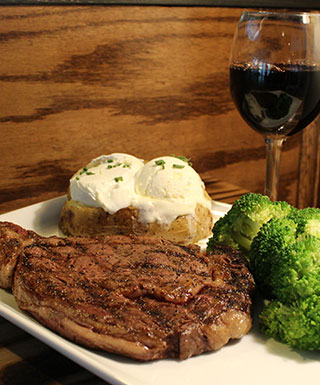 Journey steakhouse with steak, broccoli, baked potato, and glass of wine at Argosy Casino Alton.